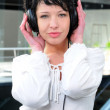 Cheerful young woman listening music with headphones — Stock Photo