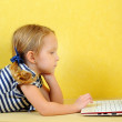 Cute little Caucasian girl using laptop while lying on floor — Stock Photo