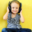Cute little girl enjoying music using headphones — Stock Photo #21637905