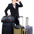 Business traveler carrying a suitcase and talking on a cell phone isolated on white background — Stock Photo