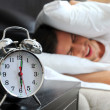 Young male adult stressed by his alarm clock with his head under the pillow in the bedroom - Stock Photo