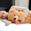 Portrait of a young man sleeping on the bed embracing his soft toy — Stock Photo