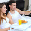 Cheerful young couple having breakfast in bed, relaxing morning — Stock Photo