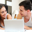 Happy couple with laptop in bed watching fun movie on computer in bed before sleeping — Stock Photo