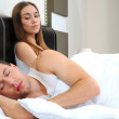 Attractive woman grieves while her husband is sleeping at home — Stock Photo