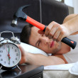 Lazy man is smashing the alarm clock with a hammer from the bed — Stock Photo #22188019