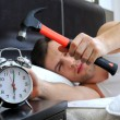 Lazy man is smashing the alarm clock with a hammer from the bed — Stock Photo