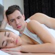 Portrait of young man looking at his wife sleeping on bed - Stockfoto