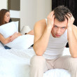 Upset man having problem sitting on the bed with his girlfriend — Stock Photo #22188159