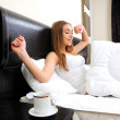 Portrait of beautiful woman with cup on bed at bedroom - Stockfoto