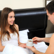 Man gives a woman a coffee in bed - Stockfoto
