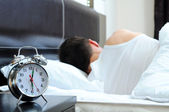 Man sleeping with alarm clock in foreground — Stockfoto