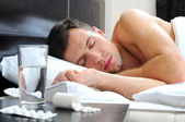 Man sleeping - pills on bed table — Stock Photo