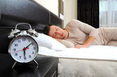 A man is sleeping with an alarm clock in front — Stock Photo