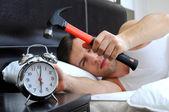 怠け者の男はベッドからハンマーで目覚まし時計を壊してください。 — ストック写真
