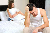 Upset man having problem sitting on the bed with his girlfriend — Stock Photo