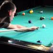 Man playing snooker in the dark club — Stock Photo