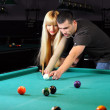 Young couple playing snooker in a billiard club — Stock Photo #22488737