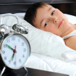 Sleeping boy with alarm clock in front - Stock Photo