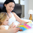 Mother and little girl reading a book - Stock Photo