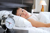 Sleeping boy with alarm clock in front — Stock Photo