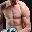 Power athletic guy , execute exercise with dumbbells, on bkack background — Stock Photo #22709073
