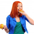 Portrait of pretty young girl deciding what to eat: an apple or hamburger — Stock fotografie