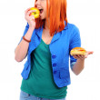 Portrait of pretty young girl deciding what to eat: an apple or hamburger — Stok fotoğraf