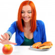 Portrait of pretty young girl deciding what to eat: an apple or hamburger — Stockfoto