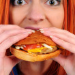 Young woman eating hamburger — Stock Photo