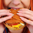 Young woman eating hamburger food — Stock Photo #22795836