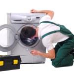 Repairman watching inside washing machine — Stock Photo #24422825