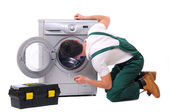 Repairman watching inside washing machine — Stock Photo