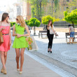 Two young women with shopping bags walking in the city — Stock Photo