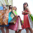 Three young women with shopping bags walking in the city - Stock Photo