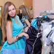 Stock Photo: Young girl in shop buying clothes