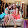 Young women with shopping bag using digital tablet — Stock Photo