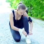 Young woman tying sports shoe — Stock Photo