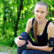 Sport woman holding her injured leg - Stock Photo
