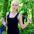 Fit girl with a jump rope in a summer park — Stock Photo
