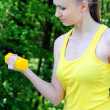 Fit woman excercising with dumbells in park — Stock Photo