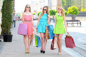 Three young women with shopping bags walking in the city — Stock Photo