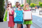 Tre giovani donne con borse per la spesa a piedi in città — Foto Stock
