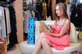 красивая женщина, улыбаясь, с ее цифрового планшета и сумки для покупок — Стоковое фото