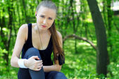 Sport woman holding her injured leg — Stock Photo