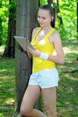 Fitness kobieta z panelem dotykowym i słuchawki pozowanie na zewnątrz — Zdjęcie stockowe