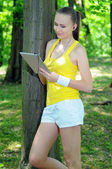 Fitness woman with touch pad and earphones posing outdoors — Stock Photo