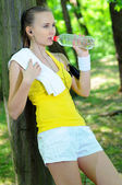 Fitness girl drinking water after training outdoors — Stok fotoğraf