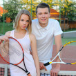 Couple playing doubles at the tennis court — Foto Stock