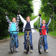 Stock Photo: Portrait of three little cyclists riding their bikes